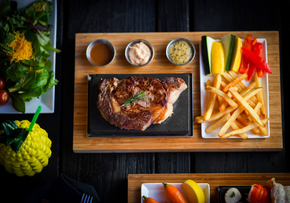 top shot of table with steak, fries and drinks
